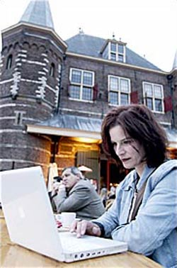 woman with laptop in front of the waag building